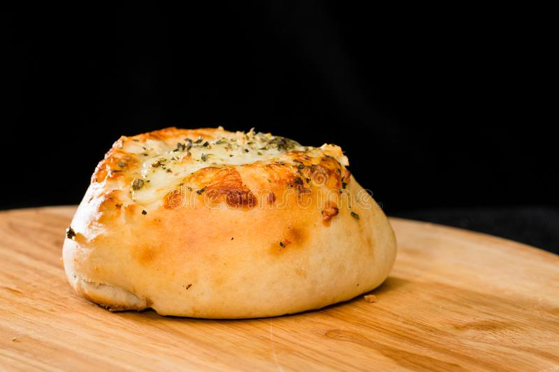 Close-up of homemade mini pizza bun topped with cheese, garlic a. Nd herbs on round wooden board on dark background royalty free stock photo