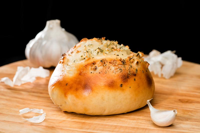 Close-up of homemade mini pizza bun topped with cheese, garlic a. Nd herbs on round wooden board on dark background, near clove garlic royalty free stock photos