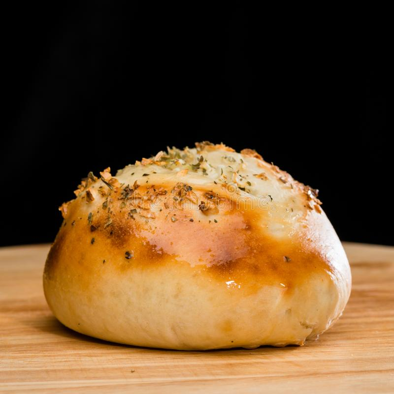 Close-up of homemade mini pizza bun topped with cheese, garlic a. Nd herbs on round wooden board on dark background royalty free stock photography