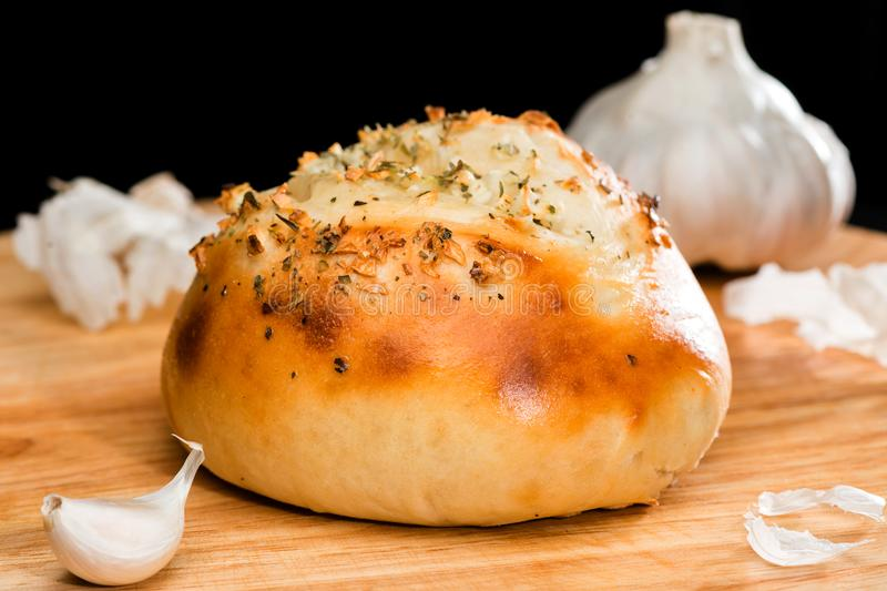 Close-up of homemade mini pizza bun topped with cheese, garlic a. Nd herbs on round wooden board on dark background, near clove garlic stock photography