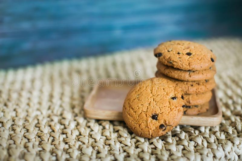 Homemade oatmeal cookies folded in a pile on wooden plate and wooden background stock images