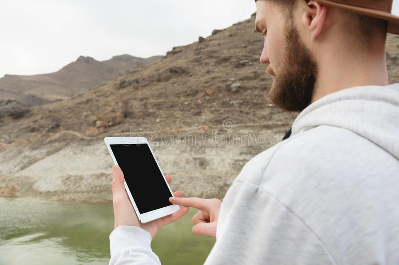 Close-up of a horde in a brown cap in the open air holds a white tablet pc in his hands. A bearded man looks at the stock image