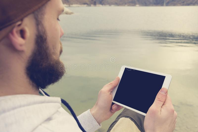 Close-up of a horde in a brown cap in the open air holds a white tablet pc in his hands. A bearded man looks at the stock photography