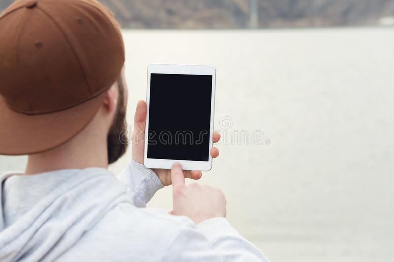 Close-up of a horde in a brown cap in the open air holds a white tablet pc in his hands. A bearded man looks at the royalty free stock image