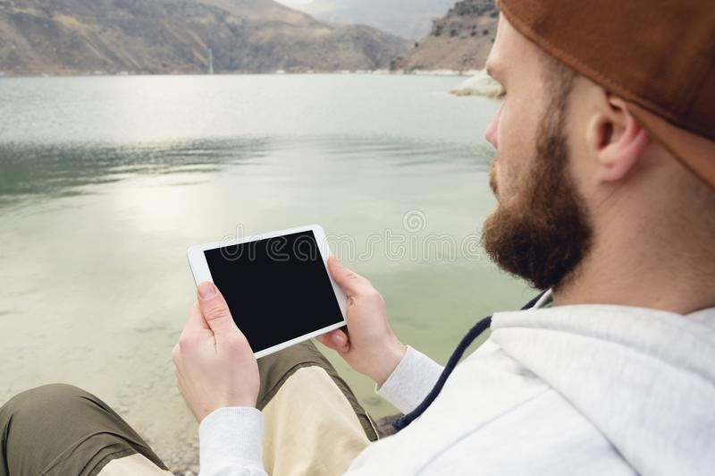 Close-up of a horde in a brown cap in the open air holds a white tablet pc in his hands. A bearded man looks at the royalty free stock photo