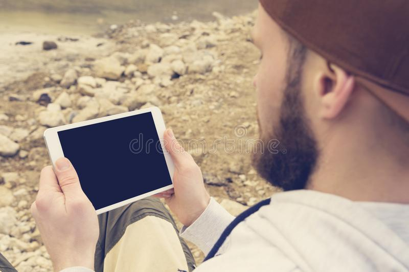 Close-up of a horde in a brown cap in the open air holds a white tablet pc in his hands. A bearded man looks at the royalty free stock images