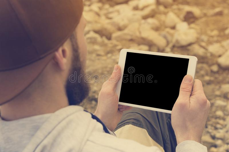 Close-up of a horde in a brown cap in the open air holds a white tablet pc in his hands. A bearded man looks at the stock photo