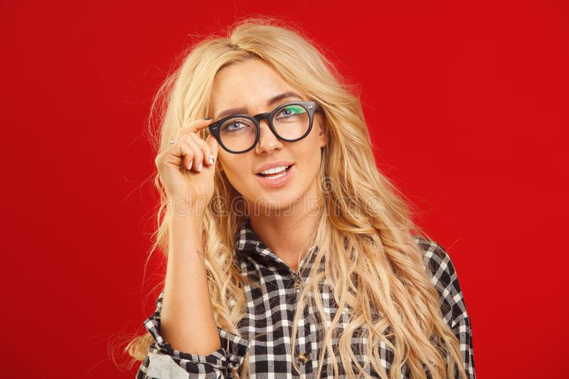Close-up horizontal female portrait of blonde with long hair in eyeglasses for vision with beautiful look looking at stock photography