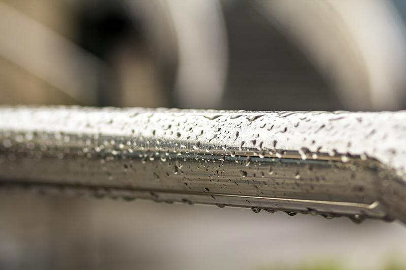 Close-up of horizontal metal wet shiny pipe with big rain water drops on blurred abstract background.  stock photography