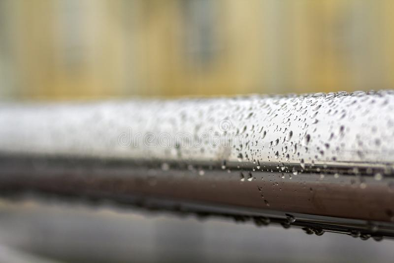 Close-up of horizontal metal wet shiny pipe with big rain water drops on blurred abstract background.  stock photos