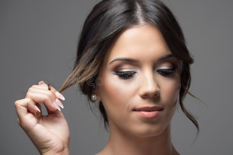 Close up horizontal portrait of young woman face with bun hairstyle holding hair lock looking down serious stock images