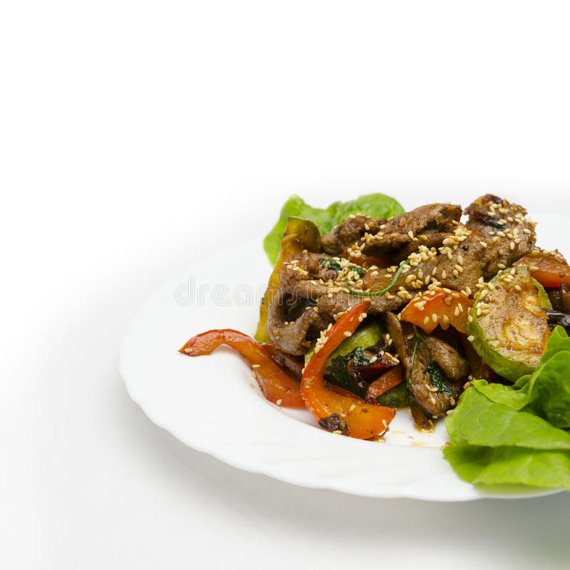 Close up hot beef on plate over white background. Juicy slices of veal with grilled vegetables under a spicy sauce, sesame emphasizes a symphony of aftertaste royalty free stock photo