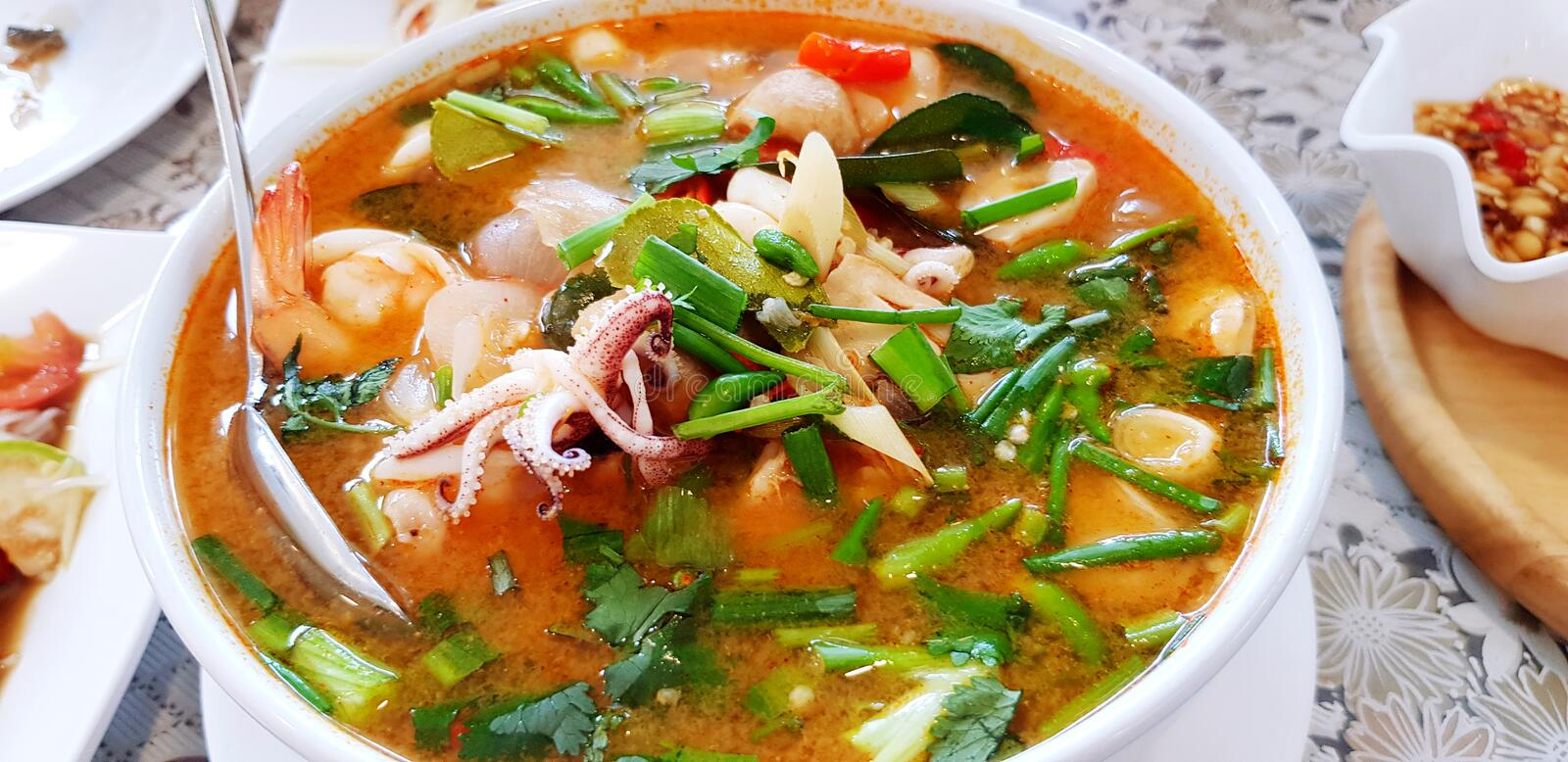 Close up hot seafood spicy soup with vegetable and spoon in white bowl on dining table for lunch time at restaurant. T royalty free stock photography