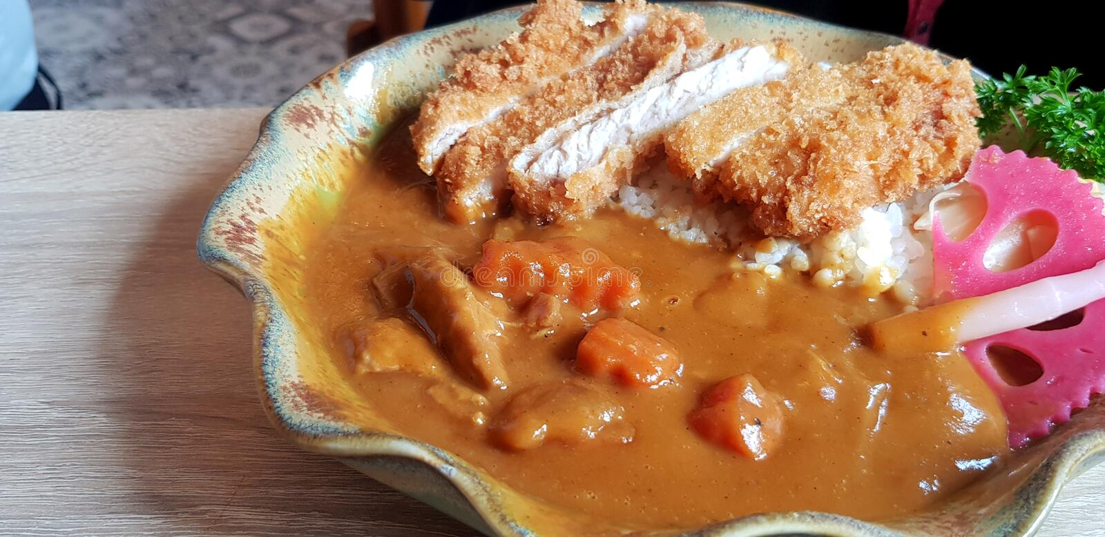 Close up hot spicy Japanese curry with fried pork and rice in plate on the wooden table royalty free stock photos