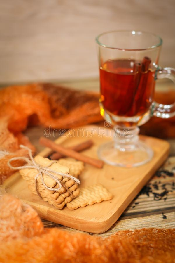 Close up hot Tea in glass cup with cinnamon sticks tea leaves and cookies on wooden table and knitted scarf around stock images