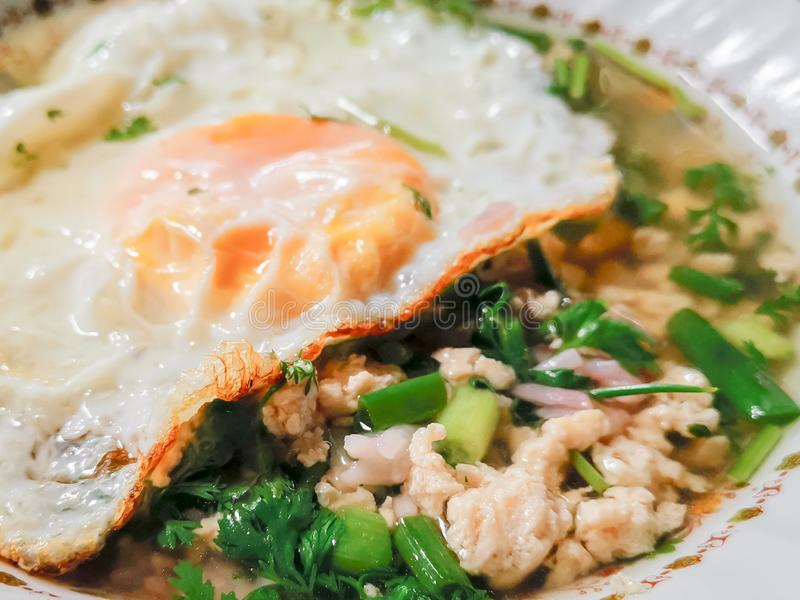 Hot Thai boiled rice soup with minced chicken, fried egg and green scallion chop in bowl. Close up Hot Thai boiled rice soup with minced chicken, fried egg and stock photography