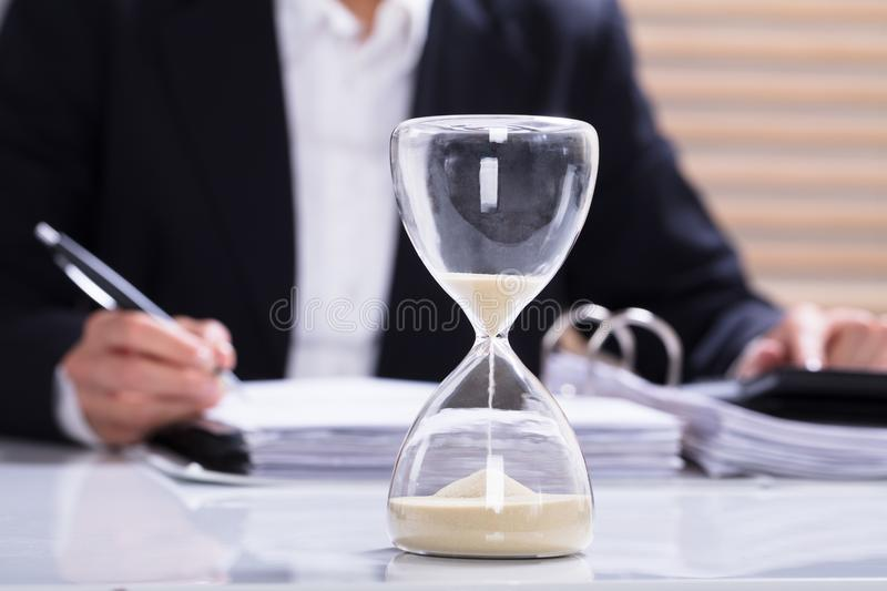 Hourglass With Businesswoman Calculating Bill royalty free stock photo
