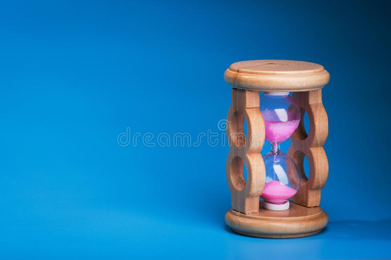 Close up of hourglass. On a blue background royalty free stock photo