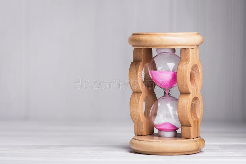 Close up of hourglass. On a white wood table royalty free stock photos