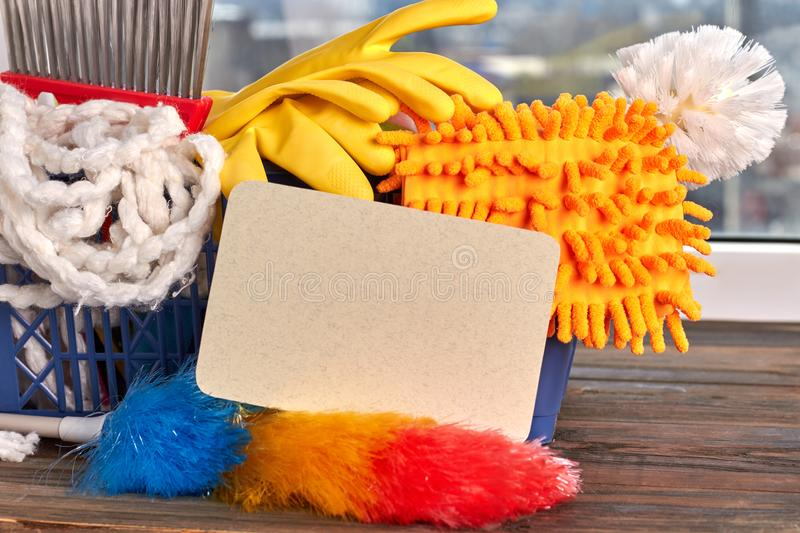 Close up house cleaning supplies. Variety of colorful house cleaning products in basket, blank paper card. House cleaning service stock image