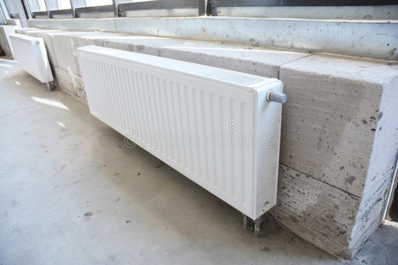 Close up on house construction heating system and radiator heating. Installing radiator heating at home.  White metal radiators stock photography