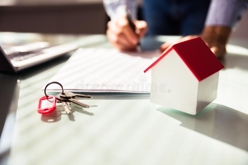 Close-up Of House Model And Key. Near Human Hand Signing Contract stock photography
