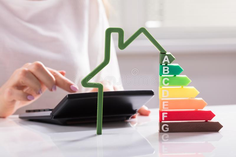 Close-up Of A House Showing Energy Efficiency Rate. In Front Of Businesswoman Using Calculator stock photography