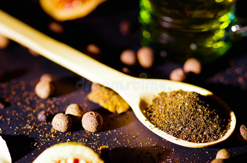 Close-up houten rustieke die lepel met vers aftrekselpoeder, andere theeën en kruiden op zeer aardige achtergrond wordt opgevuld, stock foto