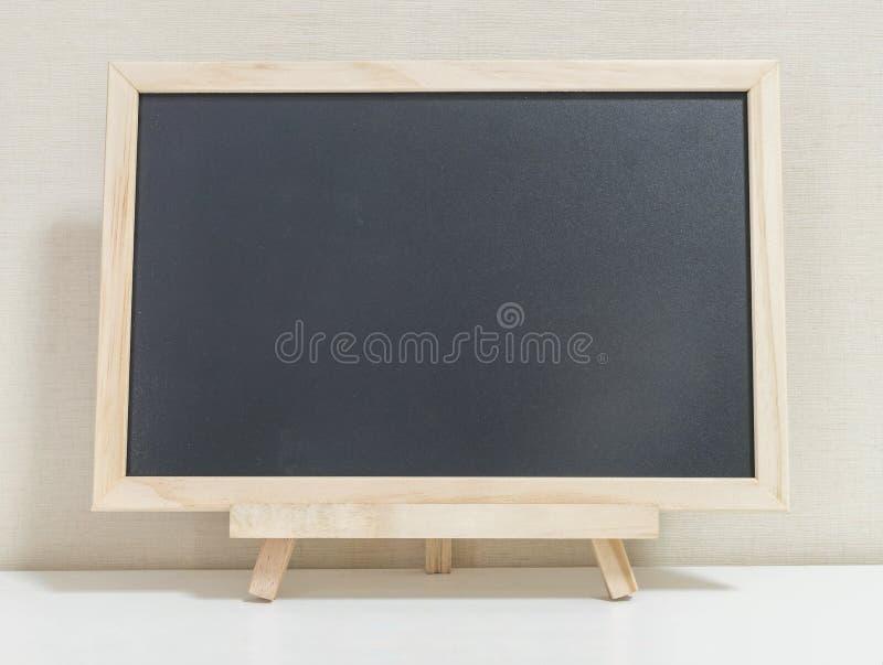 Close-up houten zwarte raad op witte houten bureau en roombehang geweven achtergrond stock afbeeldingen