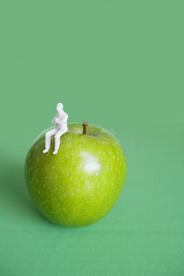 Close-up of human figurine sitting on green apple over colored background royalty free stock image