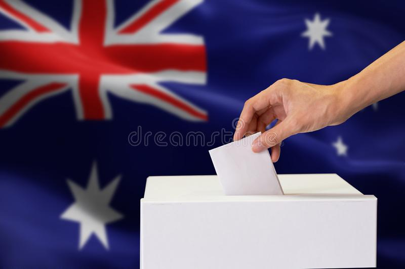 Close-up of human hand casting and inserting a vote and choosing and making a decision what he wants in polling box with Australia stock images