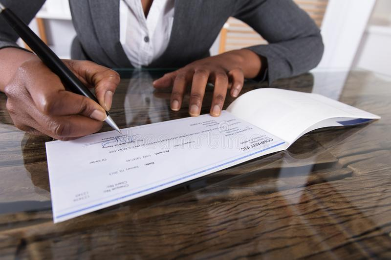 Human Hand Signing Cheque stock photo