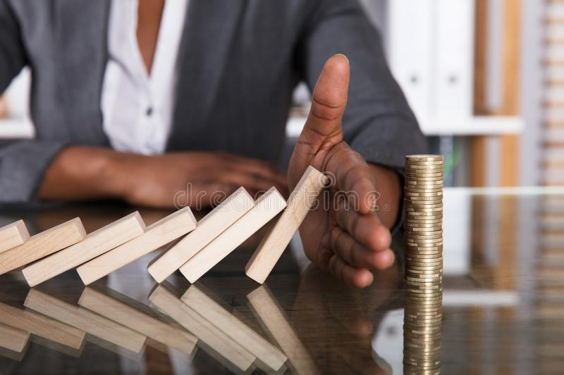 Human Hand Stopping Wooden Blocks From Falling On Stacked Coins royalty free stock photography