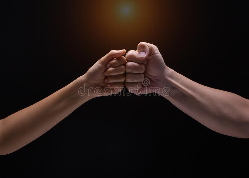 Close up of human hands making a fist bump on black background. a fist pump together after good deal stock image