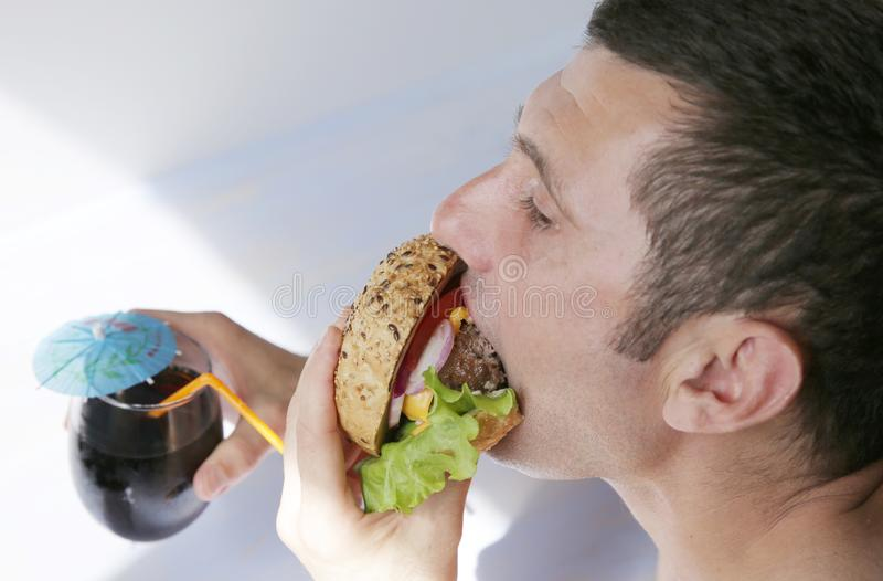 Close-up. A hungry young man eats a big hamburger sandwich with beef, tomatoes, onions, sauce, cheese, lettuce and a sesame bun royalty free stock photography