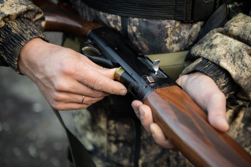 Close-up of a hunter hands loading his shotgun.  stock photography