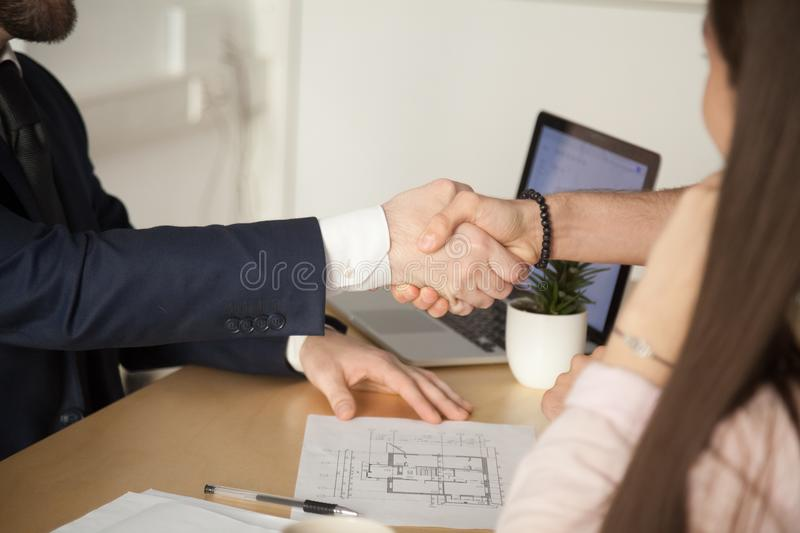 Close up of husband handshaking realtor after successful purchas. Close up of husband handshaking broker or realtor, closing successful deal on house or royalty free stock photo