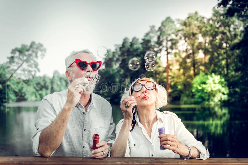 Close-up of husband and wife having fun while blowing bubbles stock images