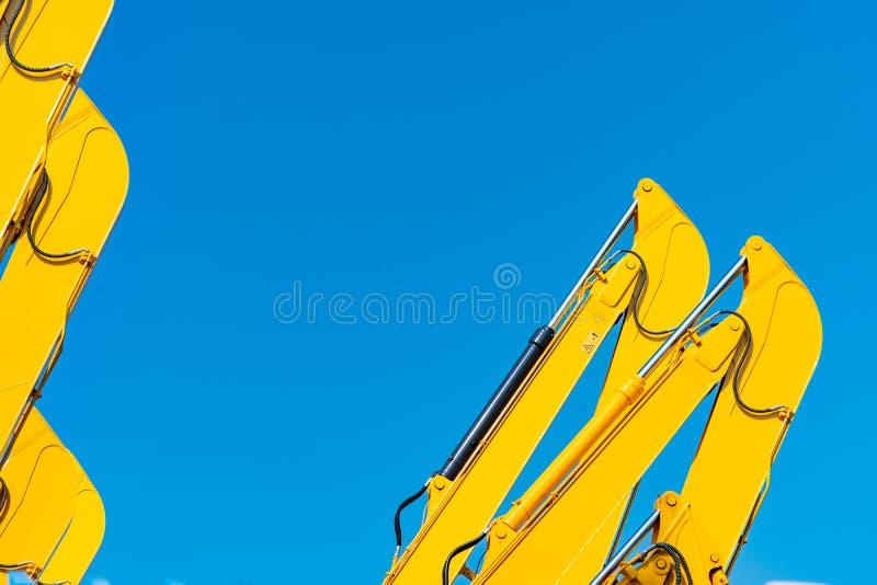Close-up hydraulische zuiger van gele backhoe tegen blauwe hemel Zware machine voor uitgraving in bouwwerf Hydraulische machine stock fotografie