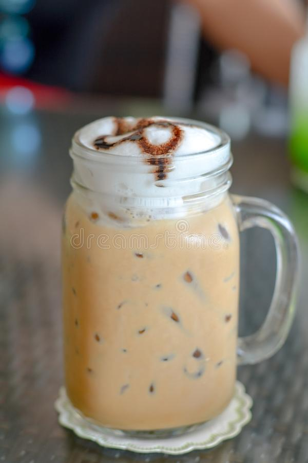 Ice coffee with milk froth in mug at cafe and restaurant. Baverage for freshness. Break times. Close up ice coffee with milk froth in mug at cafe and restaurant stock image