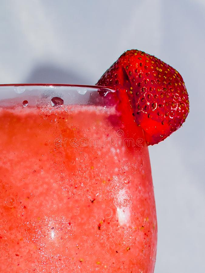 Close up of an Ice Cold Strawberry Garnish. On a frozen strawberry Daiquiri stock photos