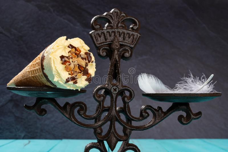 Close up of ice cream cone & feather on a balanced scale concept of non fat ice cream. Close up of ice cream cone and feather on a balanced scale concept of non royalty free stock photo
