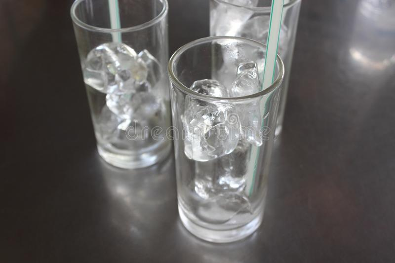 Ice cubes in glass with straw on the table. royalty free stock image