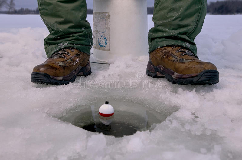 Close up of ice fisherman fishing in ice hole stock photos