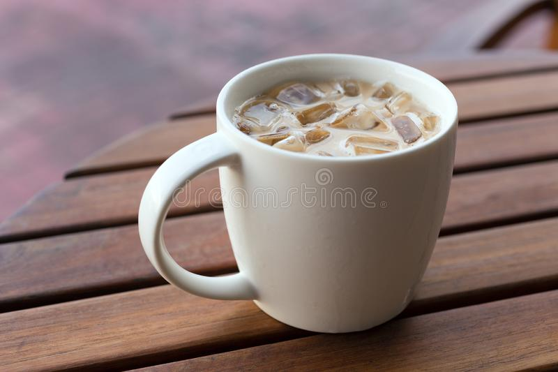 Close up of iced latte cappuccino coffee tea in a mug, wooden table background.  royalty free stock images