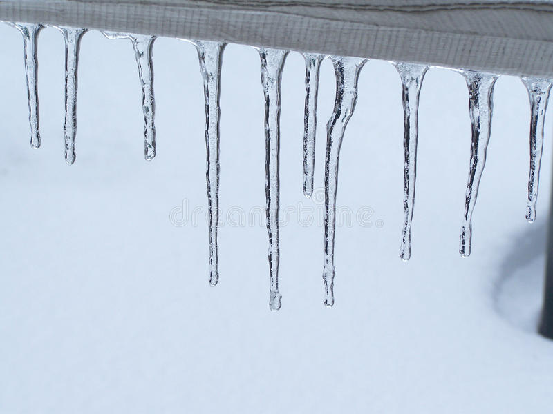 Close-Up Of Icicles On Railing-Stock photos. Close-up of icicles on a patio railing, creating a design resembling to ice teeth stock images