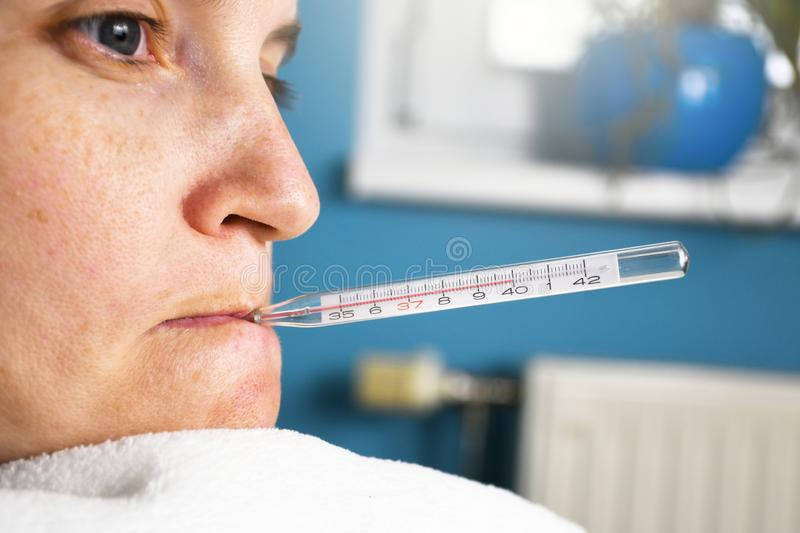 Close up of ill woman with flu and thermometer in her mouth measuring body temperature reaching 40 royalty free stock image