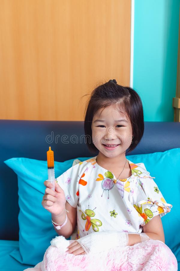 Illness asian child admitted in hospital with saline intravenous on hand royalty free stock image