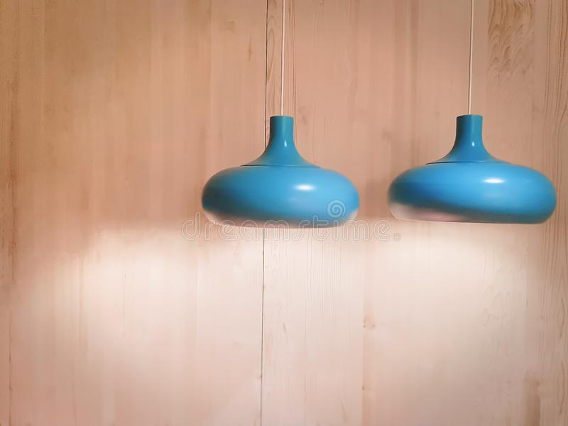 Illuminated Cyan Lamps Hanging Against Wooden Wall. Close-up Illuminated Cyan Lamps Hanging Against Wooden Wall royalty free stock photos