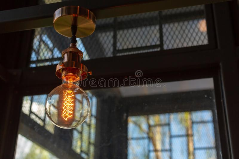 Close up of Illuminated light bulb with copy space. Architecture, art, background, black, blurred, brass, bright, classic, classical, closeup, concept, dark stock photo